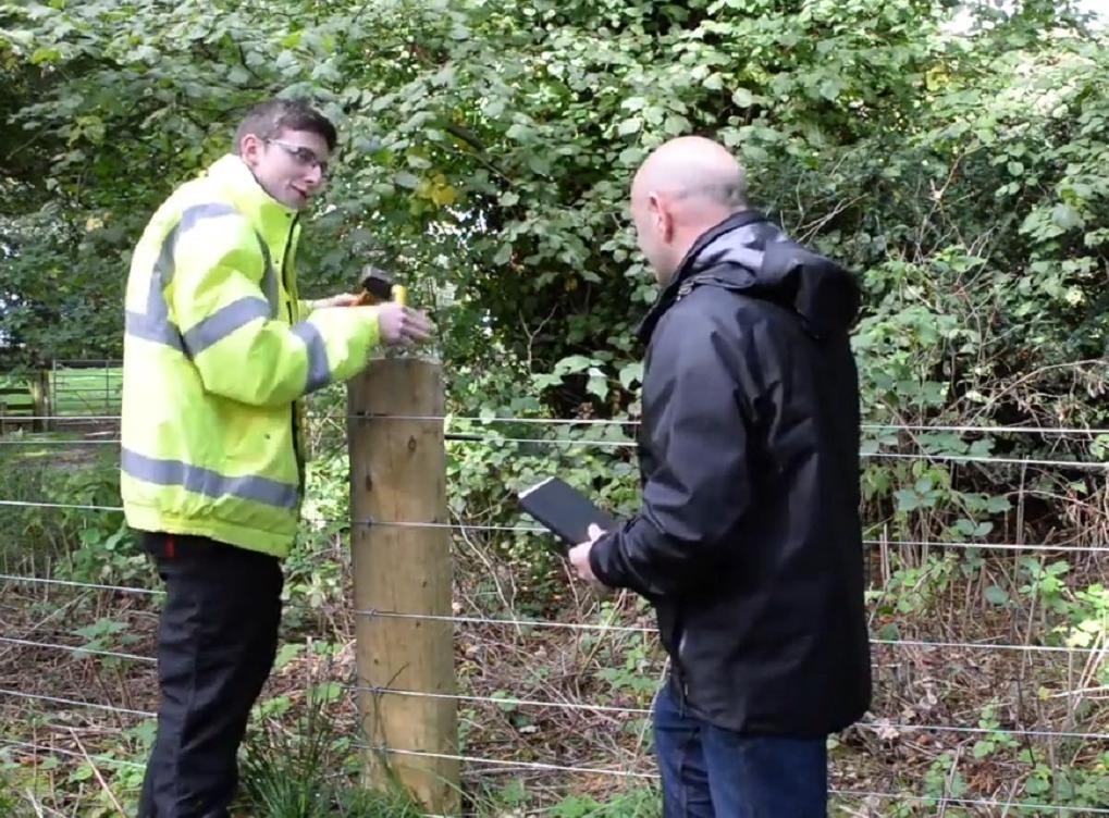 Apprentice in rural skills speaking to assessor