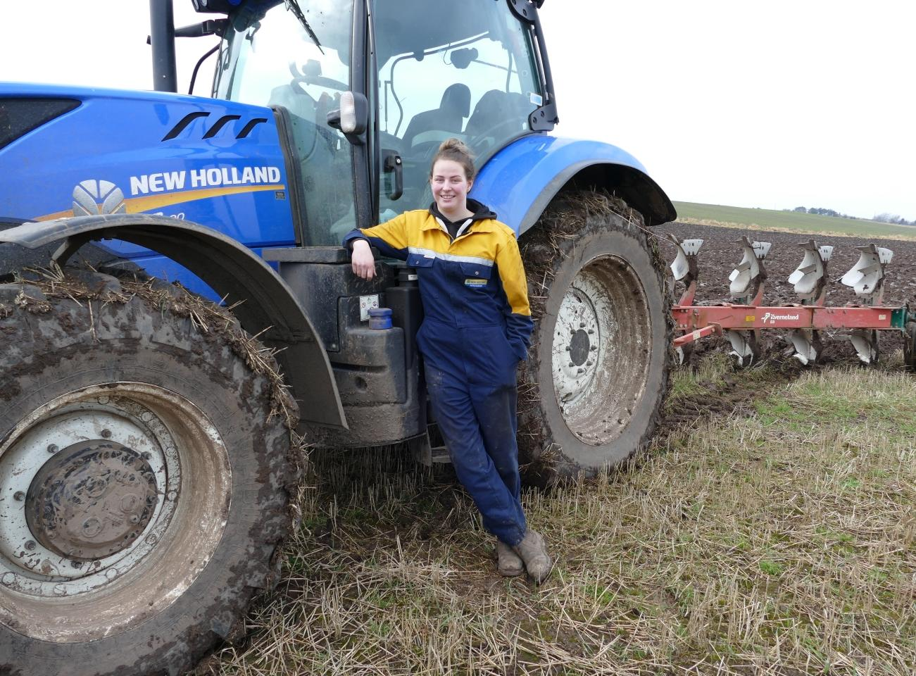 An agriculture apprentice leans against a tractor